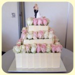 3 tier sqaure white choc chard cake with fresh pink and white roses in tiers