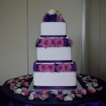 3 tier sqaure with fresh roses and lizzies between the tiers.
