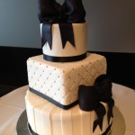 Black icing bows on a three tier fondant cake