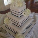 Navy criss cross ribbon on 3 tier sqaure fondant cake