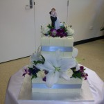 Two tier choc chard cake with silver pillars and fresh flowers