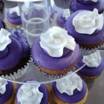 close up purple cupcakes with while frill flowers