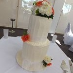 tn_Orange roses and white flowers on a two tier doucble barrel vanilla buttercream cake